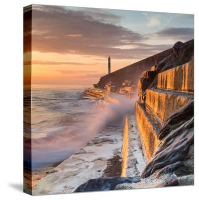 A Wave Rushes towards the Viewer along the Pier Wall at Sunset in Aberystwyth, West Wales, Uk. the-Izzy Standbridge-Stretched Canvas Print