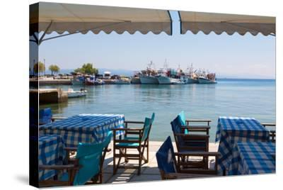 Platanias, Thessaly, Greece. Tables and chairs outside a harbour side restaurant. Fishing boats...--Stretched Canvas Print
