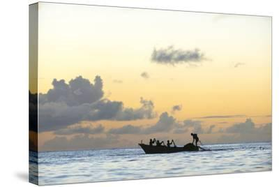 Seine fisherman lay their nets from a boat in Castara Bay in Tobago at sunset, Trinidad and Tobago-Alex Treadway-Stretched Canvas Print