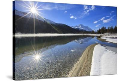 Rays of winter sun illuminate Lake Silvaplana still partially frozen Maloja Engadine Graubunden Can-ClickAlps-Stretched Canvas Print