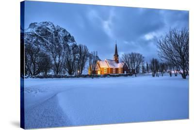 The illuminated church at dusk in the cold snowy landscape at Flakstad Lofoten Norway Europe-ClickAlps-Stretched Canvas Print