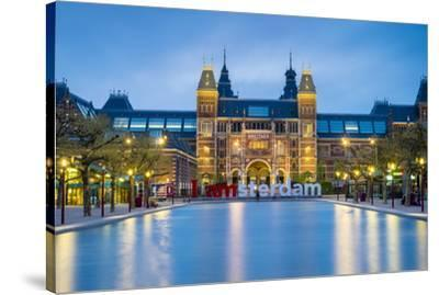 Netherlands, North Holland, Amsterdam. The Rijksmuseum on Museumplein at dusk.-Jason Langley-Stretched Canvas Print