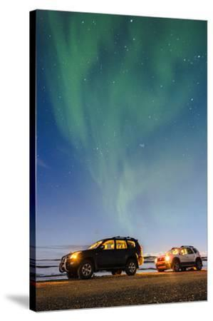 Iceland, Europe. Cars with lights on at night under a starry sky and the northern lights.-Marco Bottigelli-Stretched Canvas Print