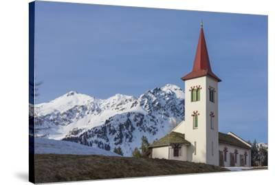 The white alpine church framed by snowy peaks, Maloja, Bregaglia Valley, Canton of Graubunden, Enga-Roberto Moiola-Stretched Canvas Print