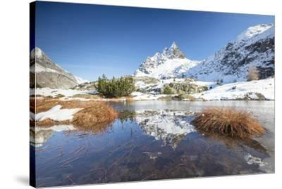 Snowy peaks are reflected in the alpine lake partially frozen, Lejets Crap Alv (Crap Alv Laiets), C-Roberto Moiola-Stretched Canvas Print