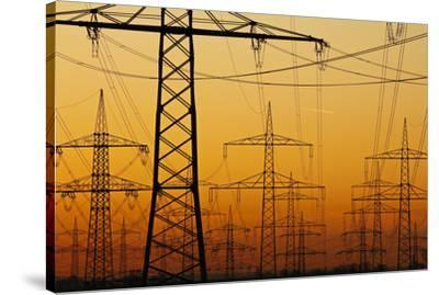 Pylons and power lines in morning light, Germany, Europe-Hans-Peter Merten-Stretched Canvas Print