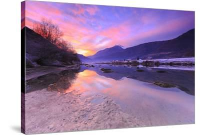 The colors of sunset are reflected in the Adda River, Valtellina, Lombardy, Italy, Europe-Francesco Bergamaschi-Stretched Canvas Print