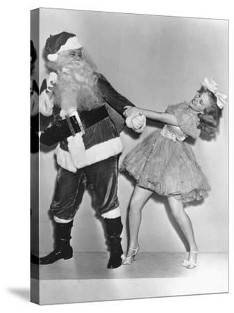 Woman Trying to Dance with Santa Claus--Stretched Canvas Print
