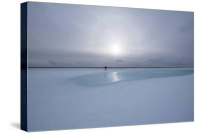 Lonely Person in Icelandic Lowlands with Blue Puddle of Water and Sun in the Background, Winter-Niki Haselwanter-Stretched Canvas Print