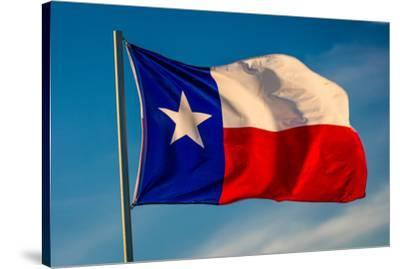 """TEXAS STATE FLAG - Texas """"Lone Star"""" flag stands out against a cloudless blue sky as it flys in...--Stretched Canvas Print"""