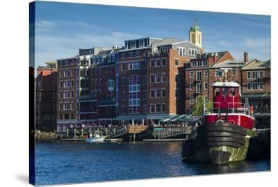 USA, New Hampshire, Portsmouth, waterfront buildings with tugboat-Walter Bibikow-Stretched Canvas Print