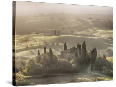 Italy, Tuscany, light filters through the fog at Belvedere House-Terry Eggers-Stretched Canvas Print