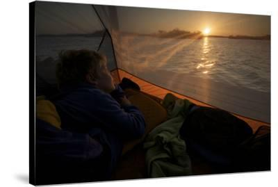 7 year old waking up at sunrise in tent on the in the mangroves.-Tim Laman-Stretched Canvas Print