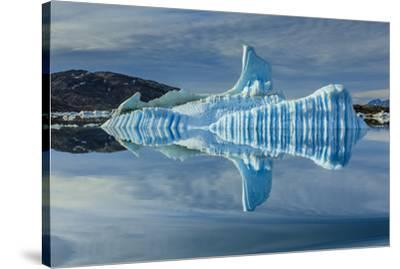 Sculpted iceberg and reflection in Semerlik Fjord.-Ralph Lee Hopkins-Stretched Canvas Print