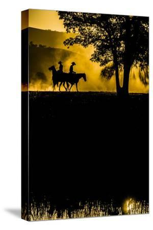 California, Parkfield, V6 Ranch silhouette of two riders faced opposite directions on horseback.-Ellen Clark-Stretched Canvas Print