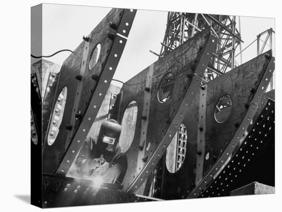 Welder Securing Steel Structure While Working on Hull of a Ship, Bethlehem Shipbuilding Drydock-Margaret Bourke-White-Stretched Canvas Print