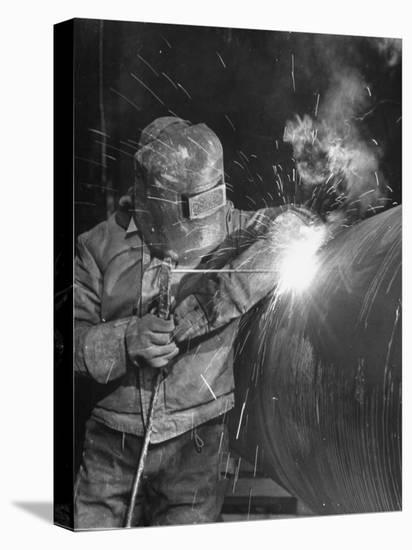 Worker Welding Pipe Used in Natural Gas Pipeline at World's Biggest Coal Fueled Generating Plant-Margaret Bourke-White-Stretched Canvas Print
