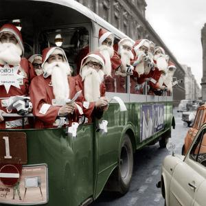 100 Santa Claus in a Special Bus in Paris December, 19, 1966. Colorized Document