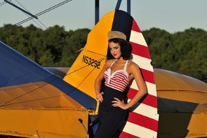 1940's Style Pin-Up Girl Leaning on the Tail Fin of a Stearman Biplane