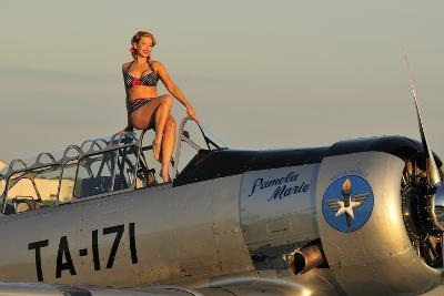 1940's Style Pin-Up Girl Sitting on the Cockpit of a World War II T-6 Texan--Photographic Print