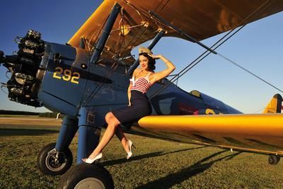 1940's Style Pin-Up Girl Sitting on the Wing of a Stearman Biplane--Photographic Print