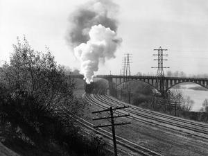 1940s Aerial of Train Traveling Along River under Bridge Billowing Smoke Near Columbus, Ohio