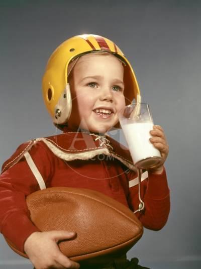 1950s 1960s Boy Drinking Glass Milk Wearing Football Helmet