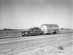 1960s-1970s Family Station Wagon and Camping Trailer Driving on Country Highway on Vacation