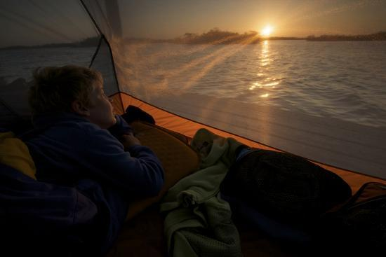 7 year old waking up at sunrise in tent on the in the mangroves.-Tim Laman-Photographic Print
