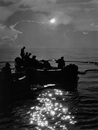 Silhouetted Watermen in their Purse Boat Laying Nets by A. Aubrey Bodine