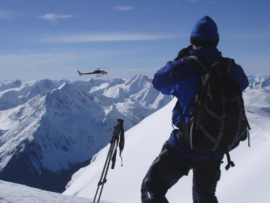 A Back-Country Skier Watches a Heli-Ski Chopper Approach a Peak-Skip Brown-Photographic Print