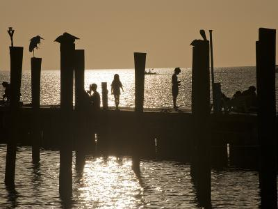 A Backlit View of People on a Pier-Karen Kasmauski-Photographic Print
