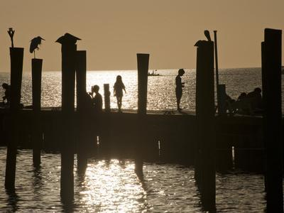 https://imgc.artprintimages.com/img/print/a-backlit-view-of-people-on-a-pier_u-l-pevs710.jpg?p=0