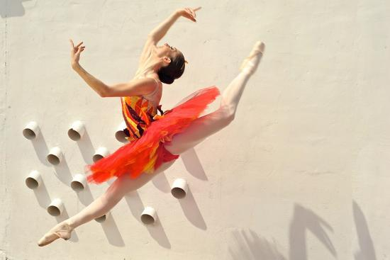 A Ballerina Dancing and Leaping Wearing a Red Dress-Kike Calvo-Photographic Print