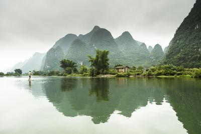 A Barefoot Man Walks Across the Li River Near Yangshuo, China-Jonathan Kingston-Photographic Print