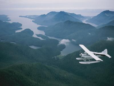 A Beaver Airplane on Floats Flies over Islands and Snowy Mountains-Joel Sartore-Photographic Print