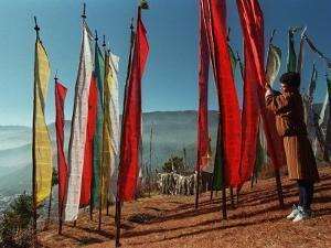 A Bhutanese Man Straightens a Prayer Flag at a Buddhist Shrine