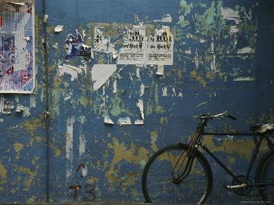 A Bicycle is Parked against a Blue Wall-Todd Gipstein-Photographic Print