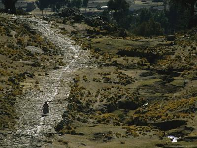 A Bolivian Woman Walks Along the Ancient Road to Tiwanaku--Photographic Print