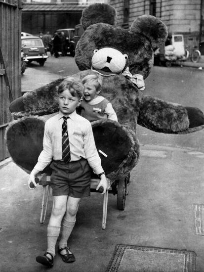 A Boy Gives a Ride to a Little Girl and a 9-Foot Teddy Bear at the Opening of the British Toy Fair--Photographic Print