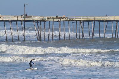 A Boy Paddles Out into Big Waves on His Standup Paddle Board Next to Nags Head Pier-Skip Brown-Photographic Print