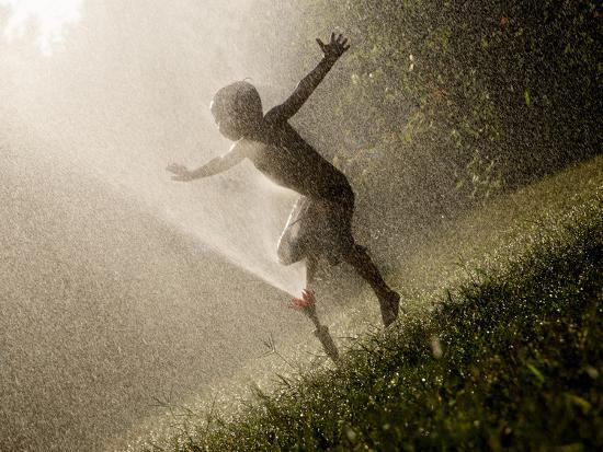 A Boy Plays in a Sprinkler on a Hot Summer Day-Heather Perry-Photographic Print