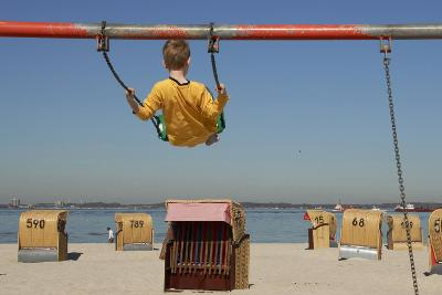 A Boy Plays on a Swing at the Beach of Laboe, Germany-Christian Hager-Photographic Print