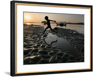 A Boy Plays on the Banks of the River Brahmaputra in Gauhati, India, Friday, October 27, 2006-Anupam Nath-Framed Photographic Print