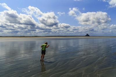 A Boy Walking Against the Wind on the Sea Floor at Mont Saint Michel Bay-Babak Tafreshi-Photographic Print