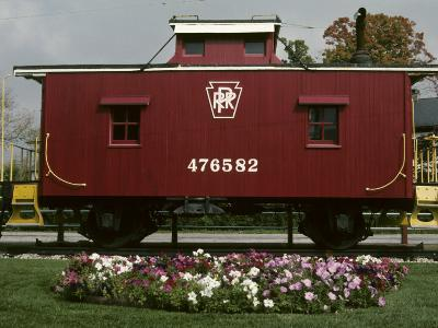 A Bright Red Caboose and a Flower Bed Compete for Vivid Color-Stephen St^ John-Photographic Print
