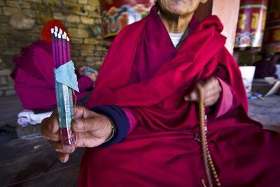 https://imgc.artprintimages.com/img/print/a-buddhist-in-red-robes-displays-burning-dhoop-whilst-seated-beside-prayer-wheels_u-l-pokg4t0.jpg?p=0