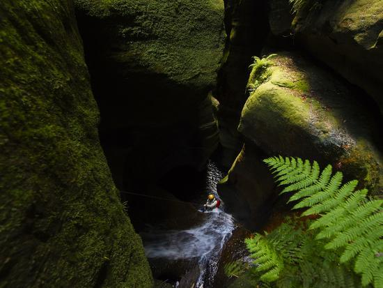 A Canyoneer Wades Through a Moss Covered Passage-Peter Carsten-Photographic Print