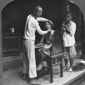 A Chinese Barber at Bhamo, Burma, 1908