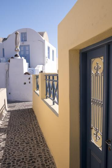A Colorful Building with a Narrow Path in the Picturesque Town of Oia, Santorini-Krista Rossow-Photographic Print